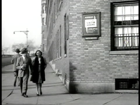 stockvideo's en b-roll-footage met urban apartment houses on long block man woman walking on sidewalk in urban city setting sign on building 'no vacancies' another sign '22 riverside... - 1946
