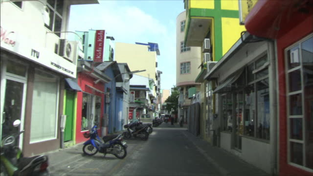 urban area; street; a row of stores: dolly shot. - alley stock videos & royalty-free footage