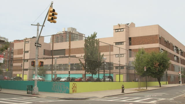 WS Urban brick school exterior with fenced parking lot and passing car - License plate blurred / New York, New York, USA
