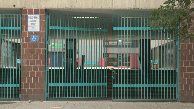 vídeos de stock e filmes b-roll de ms urban brick school gate with courtyard / new york, new york, usa - portão