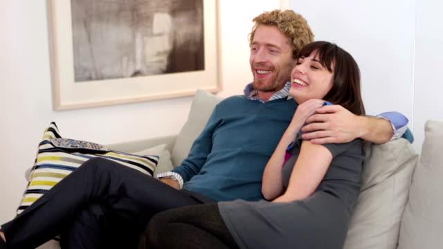 stockvideo's en b-roll-footage met urban couple watching tv slider - bank zitmeubels