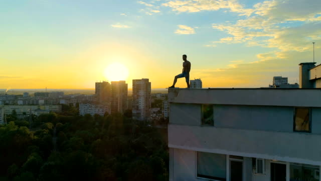 urban hero standing at the edge of a building roof at dusk - heroes stock videos & royalty-free footage