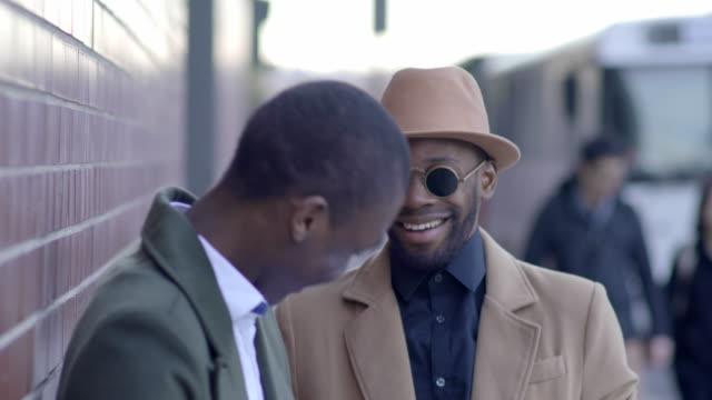 vidéos et rushes de urban lifestyle portrait of two young black african male friends talking together - couvre chef