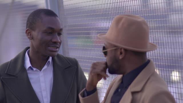 vídeos y material grabado en eventos de stock de urban lifestyle portrait of two young black african male friends talking together - beige