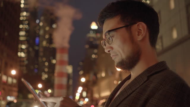 urban lifestyle portrait of young asian man using tablet computer device outdoors in the city at night - goatee stock videos & royalty-free footage