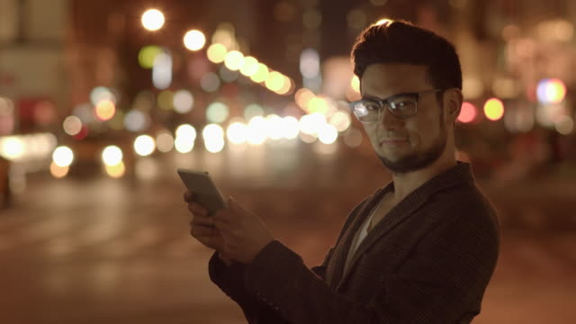 urban lifestyle portrait of young asian man using tablet computer device outdoors in the city at night - ziegenbart stock-videos und b-roll-filmmaterial