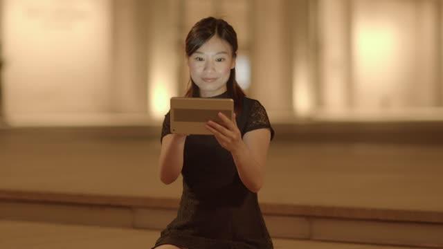 vídeos y material grabado en eventos de stock de urban lifestyle portrait of young beautiful asian women searching the internet on mobil tablet device in the city at night - sólo mujeres jóvenes