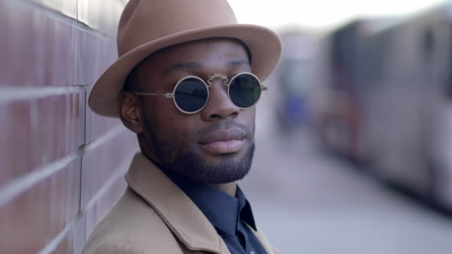 urban lifestyle portrait of young black african man wearing sun glasses in the city