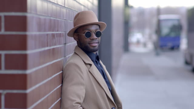 urban lifestyle portrait of young black african man wearing sun glasses in the city - beige stock videos & royalty-free footage
