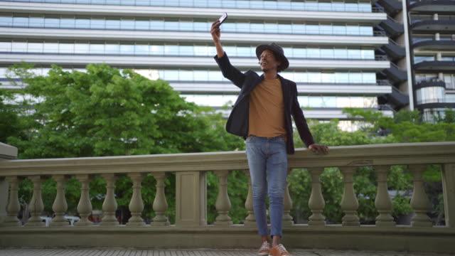 stockvideo's en b-roll-footage met stedelijke mannelijke toerist die selfie voor zijn sociale media neemt - zonnehoed hoed