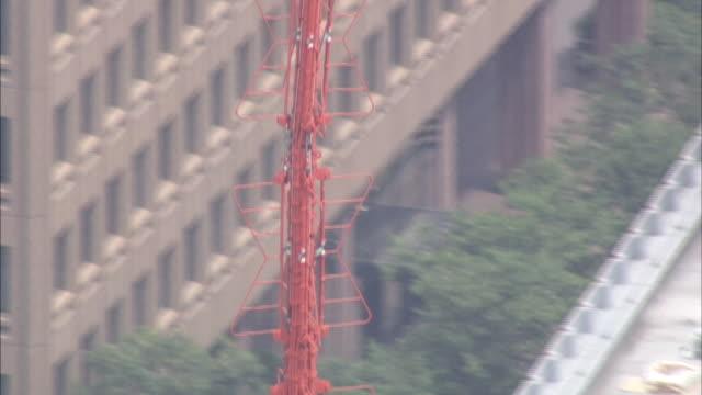 vidéos et rushes de urban neighborhoods, office buildings and other skyscrapers surround tokyo tower. - fondu de fermeture