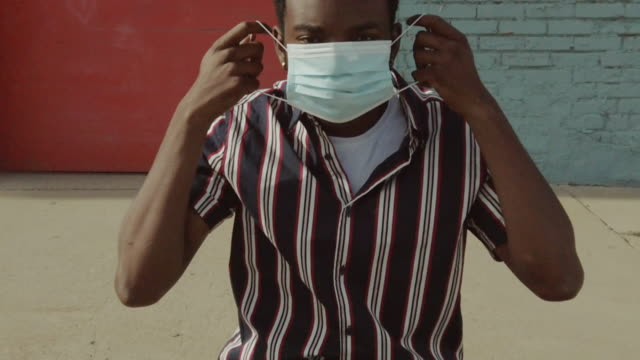 urban people black male outdoors wearing face mask during pandemic virus outbreak 4k video series - activity stock videos & royalty-free footage