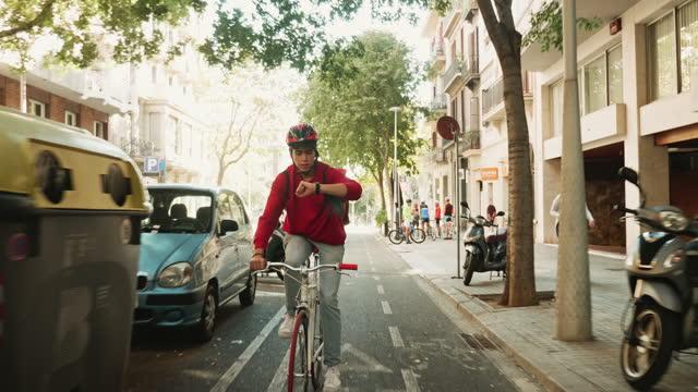 vídeos y material grabado en eventos de stock de urban pizza delivery man comprobando el tiempo mientras que el ciclismo para entregar - rucksack