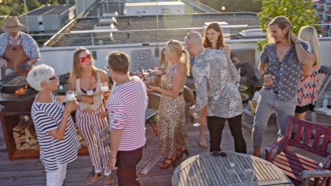 urban rooftop barbecue - 20 stylish, trendy and multicultural people enjoying a party on a roof deck while sunny summer day and a good looking woman shows up with a bowl of seafood. - after work stock videos & royalty-free footage