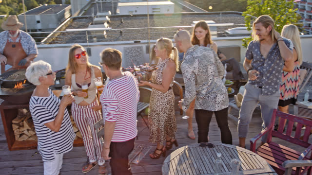 urban rooftop barbecue - 20 stylish, trendy and multicultural people enjoying a party on a roof deck while sunny summer day and a good looking woman shows up with a bowl of seafood. - party stock-videos und b-roll-filmmaterial