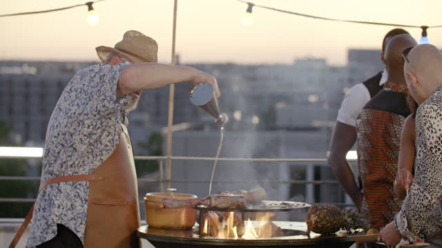 urban rooftop barbecue - chef grills big tomahawk brrf steak on flames on a roof-deck after sunset. - seasoning stock videos & royalty-free footage