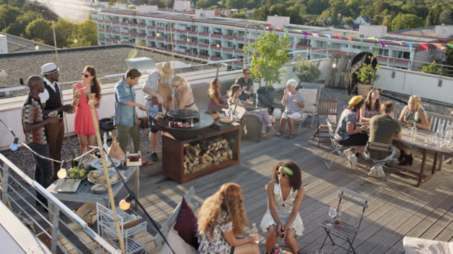 urban rooftop barbecue - crowd of 16 trendy, stylisch and multicultural people enjoying grill office party braai on a roof deck while sunny day. - patio stock videos & royalty-free footage