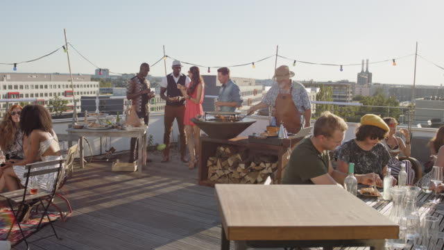 vídeos de stock e filmes b-roll de urban rooftop barbecue - group of trendy, stylish, multicultural people enjoying a grill work party braai on a sunny summer day on roof deck. - terreno