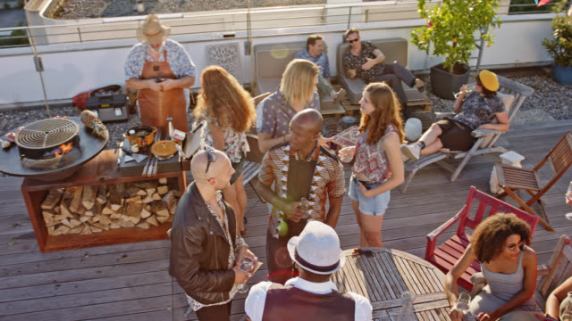 urban rooftop barbecue - stylish, trendy and multicultural group of 16 co-workers enjoying a party on roof deck while sunny summer day. - party social event bildbanksvideor och videomaterial från bakom kulisserna