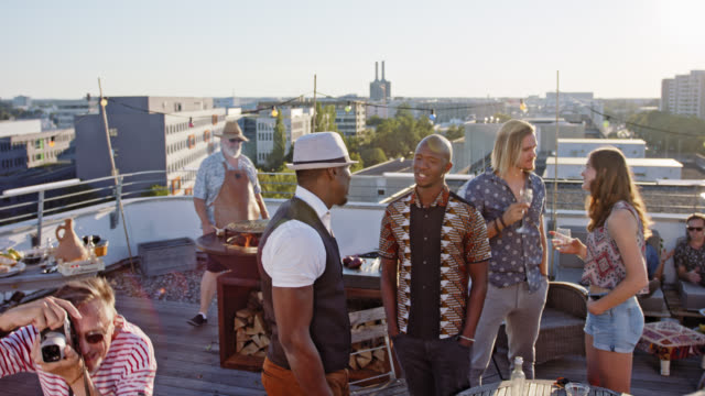 urban rooftop barbecue - stylish, trendy and multicultural people chatting, discussing and enjoying themselves while braai grill party on a roof deck on sunny summer day. - patio stock videos & royalty-free footage