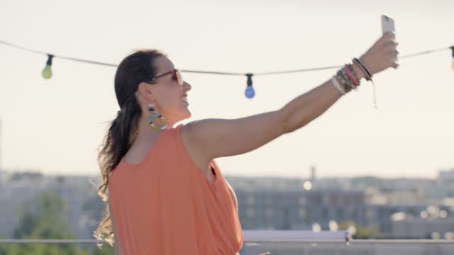 urban rooftop barbecue - sunny summer day - long lens shot - good looking girl doing a selfie / blogging - fairy lights stock-videos und b-roll-filmmaterial