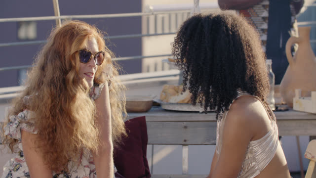 urban rooftop barbecue - sunny summer day - long lens shot - white girl and black girl discussing together - black hairy women stock videos & royalty-free footage