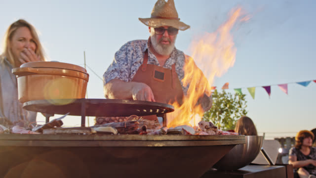 urban rooftop barbecue - the experienced chef wearing a leather apron is grilling seafood on sunny summer day. - mollusc stock videos & royalty-free footage