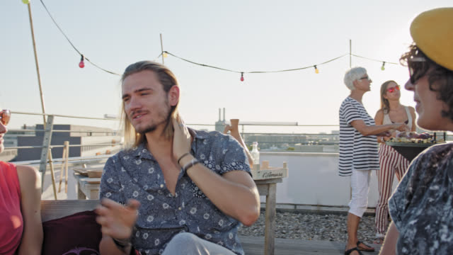 urban rooftop barbecue - trendy, stylish people chatting and enjoying themselves on roof deck while sunny summer day. - social gathering stock-videos und b-roll-filmmaterial