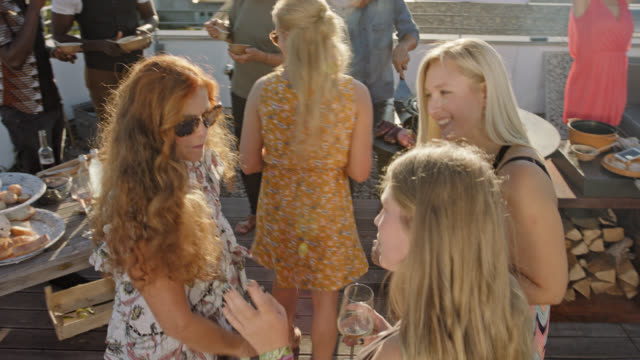 urban rooftop barbecue with trendy, stylish group of multicultural people on roof deck while sunny summer day. - party social event bildbanksvideor och videomaterial från bakom kulisserna