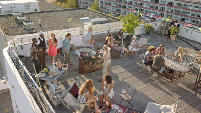vidéos et rushes de urban rooftop bbq - group of trendy, multicultural co-workers celebrating office party on sunny summer day. - toit