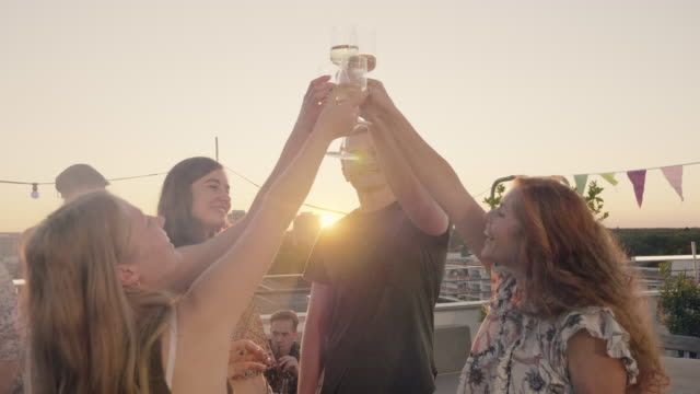 vidéos et rushes de urban rooftop party - trendy, stylish group of people celebrating on roof deck while sunny summer day -  clink glasses. - garden party
