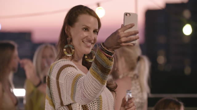 stockvideo's en b-roll-footage met urban rooftop party - trendy, stylish woman in her early 40s enjoys the party, herself and blogging while mild summer night. - oorbel