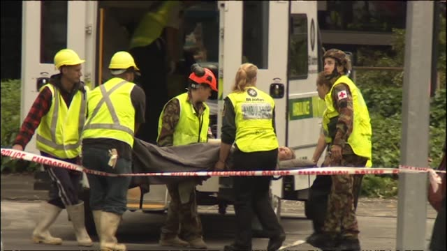 urban search and rescue team searching for people trapped inside collapsed pyne gould corporation building and rescued person being carried on... - christchurch stock-videos und b-roll-filmmaterial