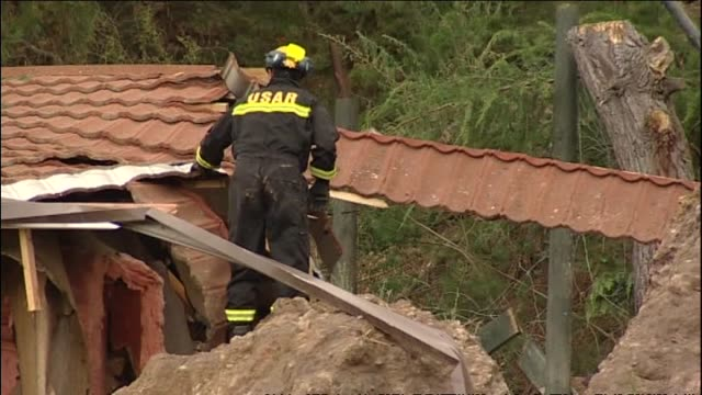 urban search and rescue workers checking out house in sumner badly damaged by slip and vehicles travelling on road with large cracks - christchurch stock-videos und b-roll-filmmaterial