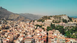 Taormina, SICILY, Italy - August 2019: Urban settlement near the rocky mountains and volcano. Red roofs of houses and people walking in the streets. Aerial drone shot