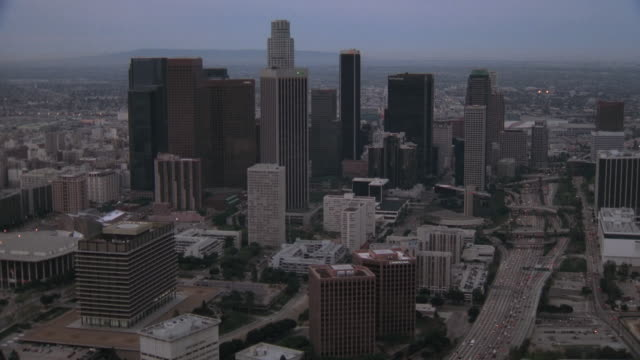 vidéos et rushes de aerial urban sprawl, the downtown skyline, and darkened skyscrapers at dawn / los angeles, california, united states - style artistique