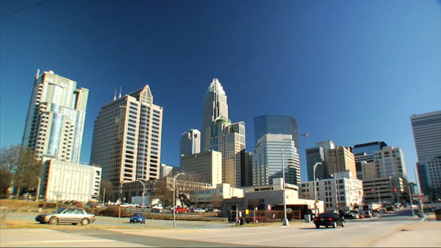 urban street in front of uptown charlotte skyline w/ skyscrapers buildings bank of america corporate center streetlights cars moving past camera in... - bロール点の映像素材/bロール
