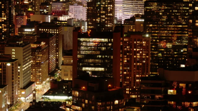urban toronto at night. tilt down from high rise to shopping street - nightlife stock videos & royalty-free footage