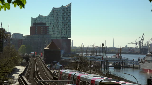 urban train at station landungsbrücken with elbe philharmonic hall, hamburg, germany - railway track stock-videos und b-roll-filmmaterial