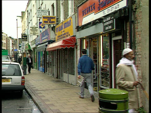 Urban UK Collection T29049416 Tower Hamlets Racism ENGLAND London Bethnal Green EXT Asian shops as music heard SOT 'Fight Racist Attacks' poster on...
