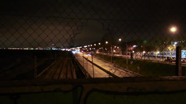 Urban view with bokeh lights of cars watched through hole from highway bridge in the grid fence.