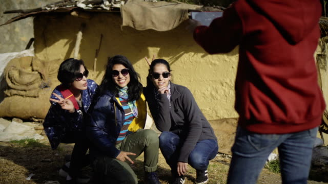 Urban young women taking pictures, having fun in a village.