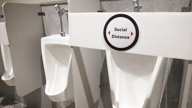 社会的な離散サインを持つ男性公衆トイレの小便器。 - 小便器点の映像素材/bロール