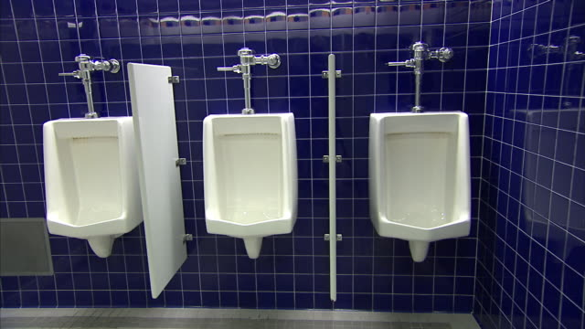 urinals line a tiled, public restroom. - urinal stock videos & royalty-free footage