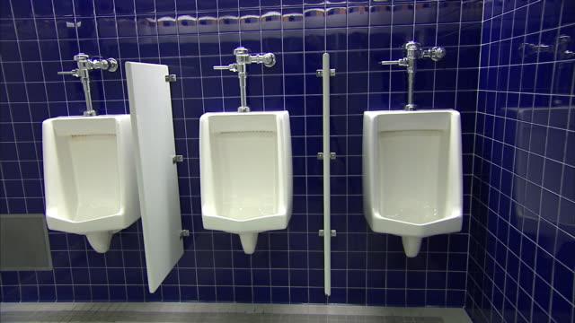 urinals line a tiled, public restroom. - 小便器点の映像素材/bロール