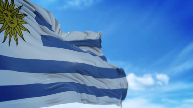 uruguaian flag is waving slowly against blue sky in 4k resolution - uruguaian flag stock videos & royalty-free footage