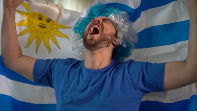 uruguayan fan celebrating at home - uruguaian flag stock videos & royalty-free footage