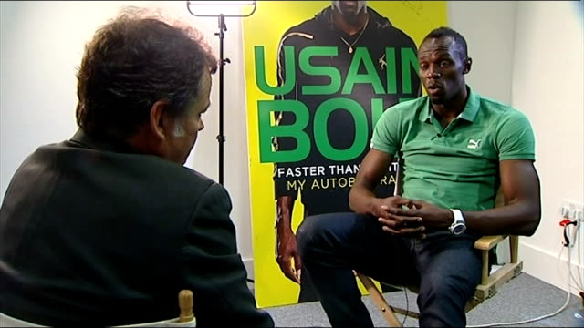 usain bolt autobiography; england: london: int usain bolt sitting chatting with reporter with blown up cover of his autobiography in background usain... - autobiography stock videos & royalty-free footage