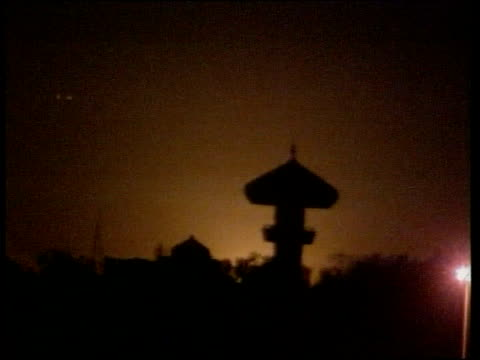 baghdad sky lit up by explosion in distance another explosion silhouetting minaret of mosque sparks and smoke rising from explosion cruise missile... - luftvärn bildbanksvideor och videomaterial från bakom kulisserna