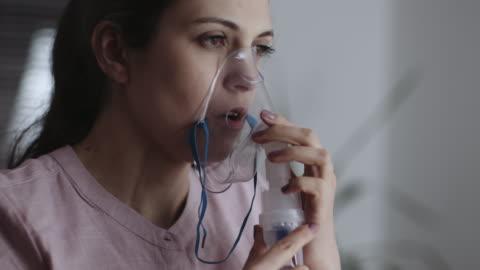 vídeos de stock e filmes b-roll de use nebulizer and inhaler for the treatment. young woman inhaling through inhaler mask. stock video - equipamento respiratório